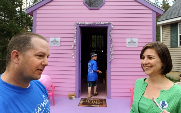 Brian and Tracy McKenney talk outside as their son Nathan,6, (center) walks into the new playhouse donated to his sister nine-year-old Caitlin. The young girl was honored with a parade through town Friday and the surprise was the playhouse donated by the Make-A-Wish Foundation of Maine.
