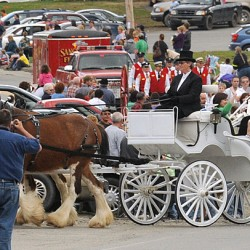The parade honoring Caitlin McKenney who got to ride in the white horse-drawn carridge winds through Harmony Friday. Hundreds of people lined the streets and participated.