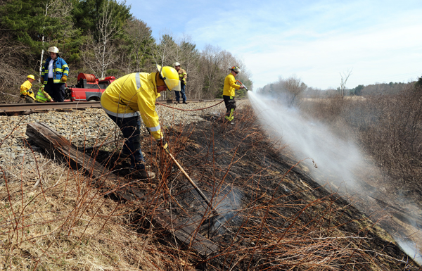 Firefighters from Carmel, Etna and Levant work to put out hot spots along railroad tracks near the town's recreation fields on Tuesday.