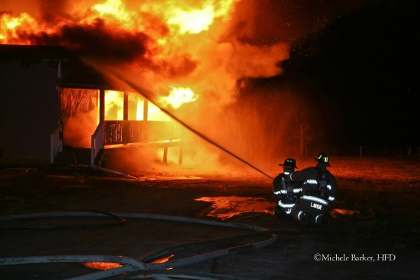 Firefighters from Glenburn Fire Department attack an early Wednesday morning fire in Charleston from the side of the home.  The firefighter at right is Chris Lavoie from Glenburn Fire.