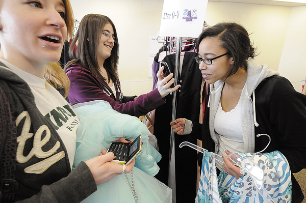 Maria Hustus (left), 17 of Searsport and Hannah Betit (right), 17 of Searsport get help with their prom dress selections from friend and volunteer Alicia Lane (center) of Searsport as she shows cell phone pictures of their selections during the 6th annual Cinderella Project of Maine prom dress giveaway at Reny's Plaza in Belfast Saturday morning.