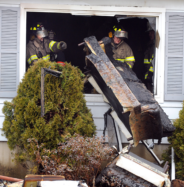 Firefighters toss charred furniture from a home on the County Road in Corinth after they put out the fire Tuesday afternoon.  Crews from Corinth, Hudson, Kenduskeag, Bradford, Levant, Garland and Charleston responded to the call.