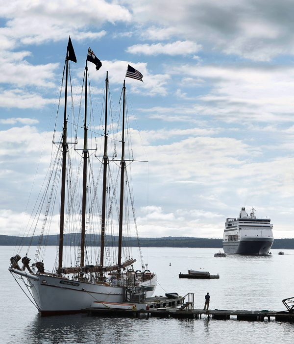 The Maasdam, a 1258-passenger cruise ship, sits at anchor in Frenchman's Bay off Bar Harbor in June 2010. A four-masted windjammer is docked in the foreground.