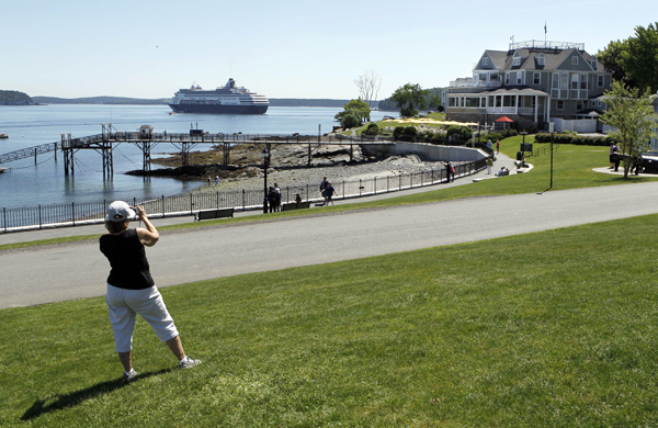 A tourist photographs a scene that includes the 719-foot cruise ship Maasdam and the Bar Harbor Inn in Bar Harbor in 2010.