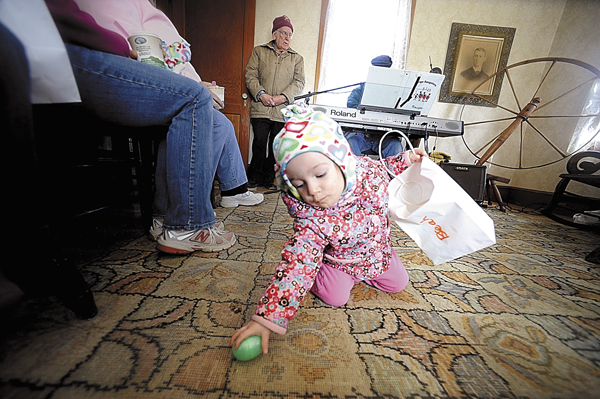 Breah Curtis of Newburgh retrieves an Easter egg that fell from her bag as she and her big sister Molly Curtis, 3 and her mom Amy Curtis (both not pictured) listened to Bangor musician and Curran Homestead board member Jerry Hughes (in background) play old time favorites on his keyboard at the Curran Homestead in March 2010.