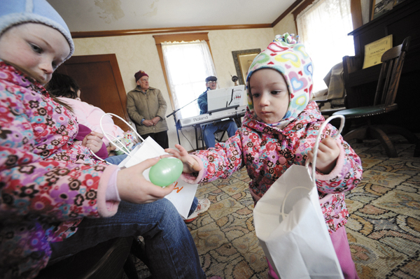 Breah Curtis of Newburgh grabs a plastic Easter egg from her big sister Molly Curtis (left), as they and their mom Amy Curtis (not pictured) listened to Bangor musician and Curran Homestead board member Jerry Hughes (in background) play old time favorites on his keyboard at the Curran Homestead in March 2010.