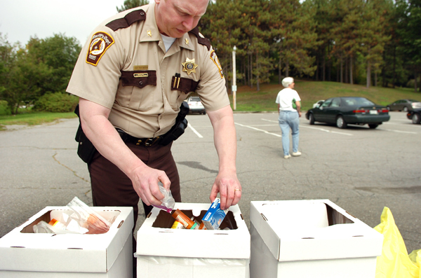 Chief Troy Morton with the Penobscot County Sheriff's Department dispenses drugs into containers which were turned in by community members as part of a national prescription drug take-back campaign at Cascade Park in Bangor in Sept. 2010.