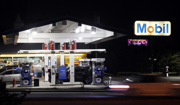 A man pumps gas as a car whizzes by a Mobil Station in Stoneham, Mass. Exxon Mobil Corp. increased earnings even though it produced less oil and natural gas liquids.