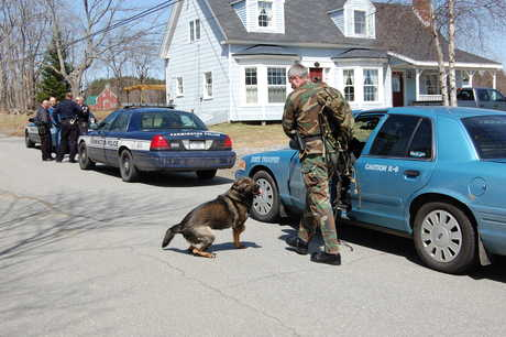 Maine State Police Trooper Matt Casavant prepares to take his tracking dog, Marcello, into the woods Thursday to find suspects in a home burglary on Red School House Road in Farmington.