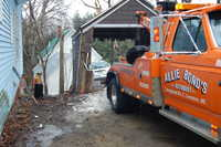 Allie Bond's Autobody winches a minivan out of a house on School Street in Livermorre Falls back through a garage on High Street it went through Wednesday after it lost its brakes.