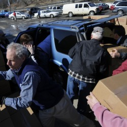 George Manlove (lower left) and other members of the Star Riding and Touring Association joined other volunteers in the parking lot of Manna Inc. Friday morning to load boxes of food and personal care items into vehicles for local distribution. Feed the Children brought a semi tractor trailer filled with food and other essentials to help 400 area families.