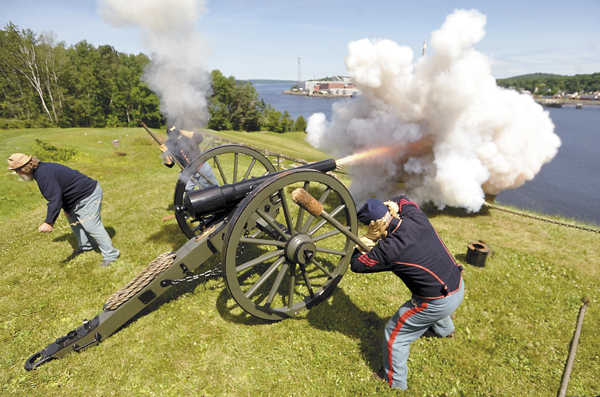 Members of the 6th Maine Light Artillery, a Civil War re-enactment group, cover their ears as they touch off the sonorous firepower of a reproduction of a Civil War-era 10-pound Parrott rifle at Fort Knox in 2010.