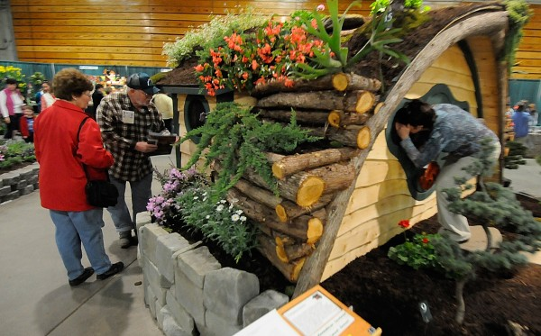 Angela Guiggey (right) of Silver Ridge Township peers through a window in the white pine construction &quotHobbit Hole&quot — part of the gardenscape created by Unity-based Moonshine Gardens at Bangor's Garden Show. The three-day show, which ended Sunday, featured eight gardenscapes by area designers as well as vendor booths and demonstrations. Photographed Sunday, April 10, 2011.