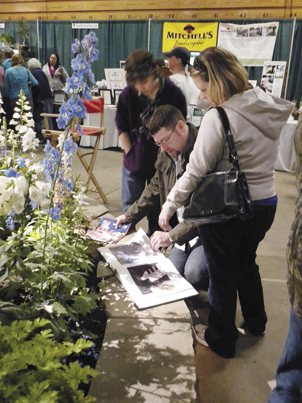 Milford residents Jerrett and Alexi Greenleaf thumb through a display book of before and after landscaping shots at the 20th annual Bangor Garden Show on Saturday while nephew Teddy Hanson looked on.