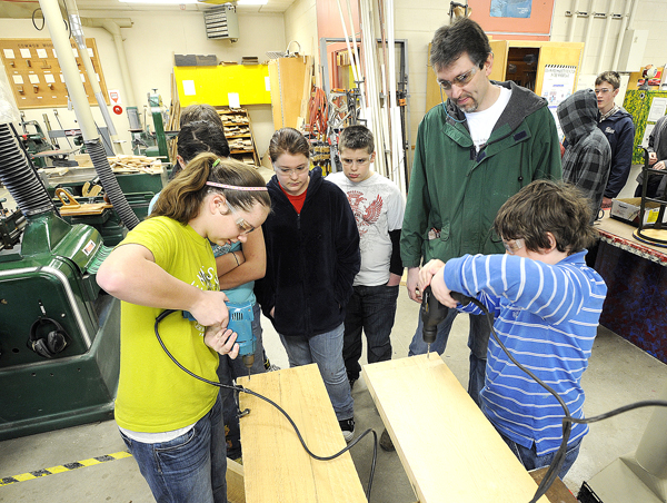 Auburn Middle School students Sarah Knoblach, 12, (left) and Zach Johnson, 13, (right) drill holes for garden boxes Monday. Teacher Jim Rowe, (back right) supervises. A few days before Earth Day, teachers and students volunteered to get the boxes built and outside.