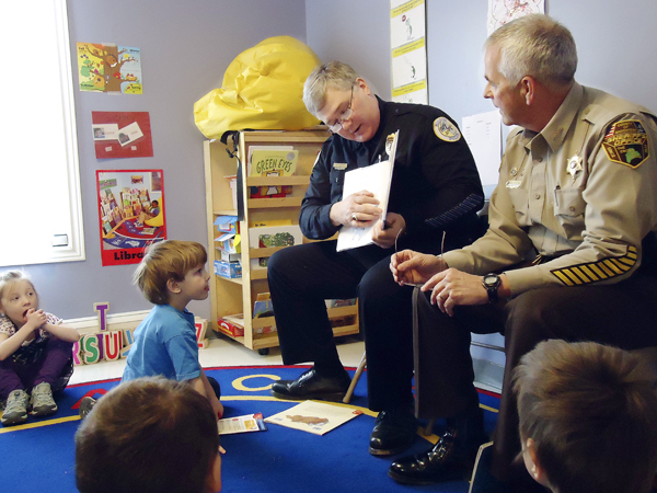 Houlton Police Chief Butch Asselin, left, and Aroostook County Sheriff Jim Madore read a book to children in the early learning program at the Houlton Head Start Center on Monday. The initiative was organized by the national anti-crime organization Fight Crime: Invest in Kids. Both Madore and Asselin are members of the campaign to promote support for investing educationally in children at an early age.