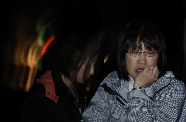 A Japanese woman reacts Friday, April 8, 2011 in Ishinomaki, Iwate Prefecture, northern Japan, after a 7.4-magnitude earthquake struck offshore, late Thursday.