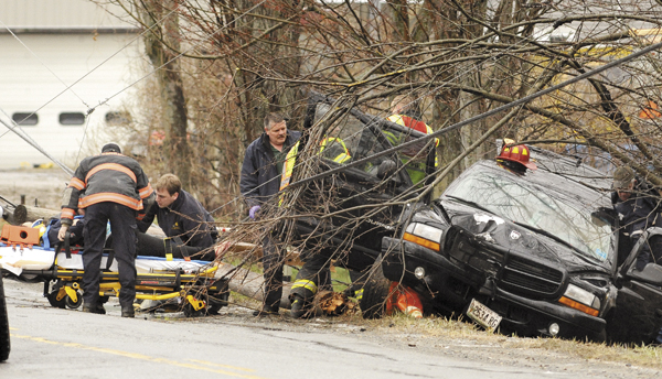 First responders attend to a woman (left) after she was taken out of a vehicle that crashed on the Stetson Road in Kenduskeag Wednesday.  The SUV skidded off the road and broke a utility pole bringing the wires down.  The rescue crews had to wait about ten minutes to extract the two occupants of the vehicle because the live power lines were touching the vehicle. The extent of the injuries was not available on the scene and Penobscot County Sheriff's Deputy Steve Saucier said that the road conditions could have contributed to the accident that is under investigation.