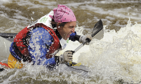A competitor reacts as his canoe gets swamped with cold water at the 'Shopping Cart' during the 45th annual Kenduskeag Stream Race with the time of 1:59:35.