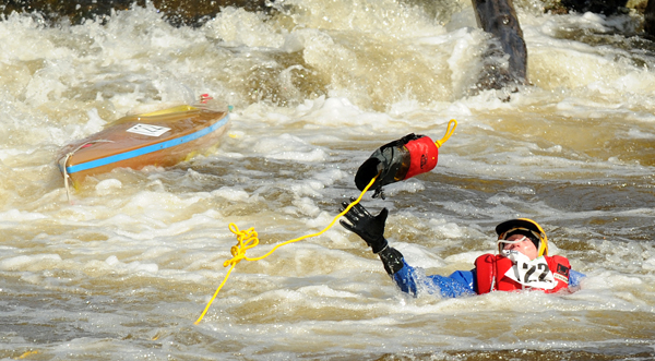 A kayaker reaches for the rope thrown by a rescuer after he failed to negotiate the rapids at Six Mile Falls during the 45th annual Kenduskeag Stream Race Saturday.