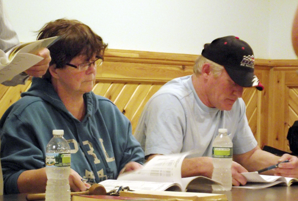 Virginia McCain, left, and Greg Dow, two members of the Ludlow Board of Selectmen, review financial statements during the annual town meeting on Monday evening. Approximately 40 residents attended the nearly two-hour meeting. Although voters made some cuts to the overall budget, the mill rate in the community is still expected to rise by three to four mills.