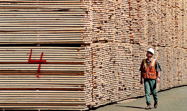 A worker at a lumber mill in British Columbia walks past softwood lumber ready to be shipped in this file photo. A group representing U.S. lumber interests says the 2006 trade agreement with Canada is working, but investigations into potential violations have been slowed by international politics.