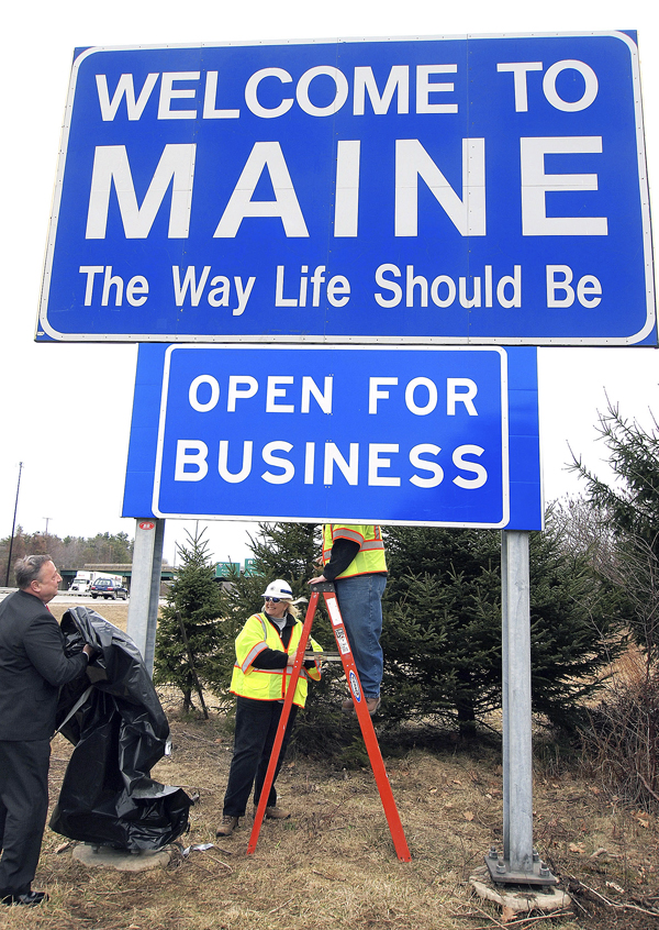 Maine Gov. Paul LePage (left) unveiled a new &quotOpen for Business&quot sign beneath the &quotWelcome to Maine&quot sign along Interstate 95 near the New Hampshire border in Kittery. Maine Department of Transportation crew supervisors Elaine Cota (center) and Aaron Main (on ladder) assist. The ceremonial event helped fulfill LePage's campaign promise to bring jobs to the state.