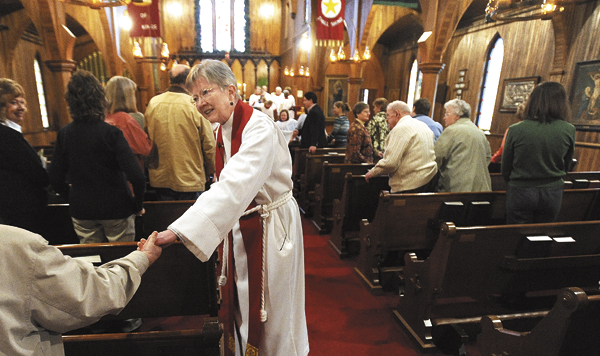 The Rev. Leslie Nesin shakes hands with parishioners during the Palm Sunday service at the Chuch of the Good Sheperd in Houlton.  Reverend Nesin is retiring at the end of May.