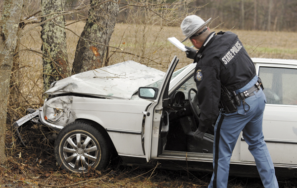 State Police Trooper Doug Franklin inspects the damage to a Mercedes Benz after it was crashed on the Griffin Road in Levant on Wednesday. 