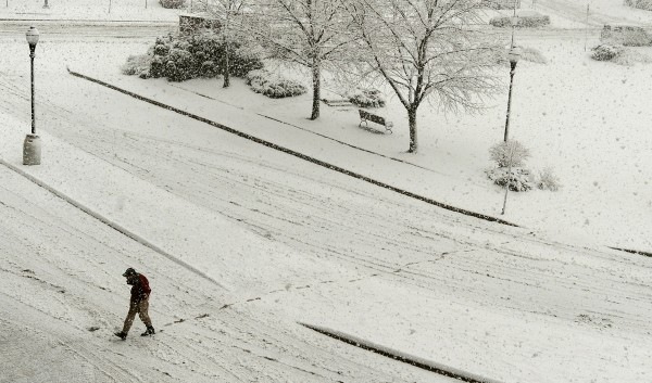 A man walks across Pickering Square in Bangor during Friday's snow storm.