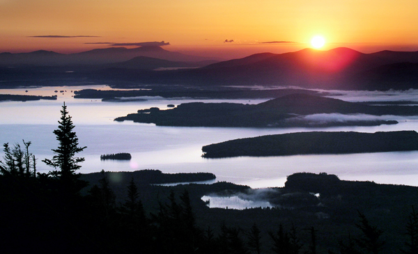 The sun rises over the mountains east of Moosehead Lake in this view from the summit of Big Moose Mountain near Greenville in 2004.