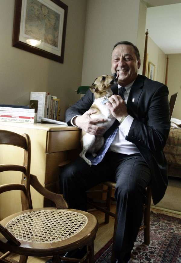 Gov. Paul LePage holds his dog, Baxter, as he poses by furniture he made at his home in Waterville in June 2010. Baxter now has his own blog.