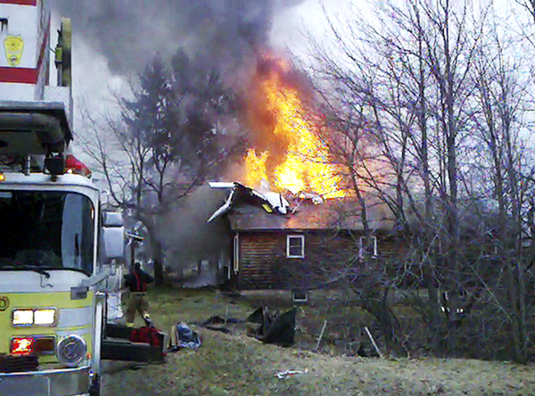 This still image from cell phone video provided by Sheila Gagne Conley shows the wreckage of a small plane atop a house on fire near the Biddeford, Maine, Municipal Airport Sunday evening, April 10, 2011. The Federal Aviation Administration said the pilot of the plane died in the crash.