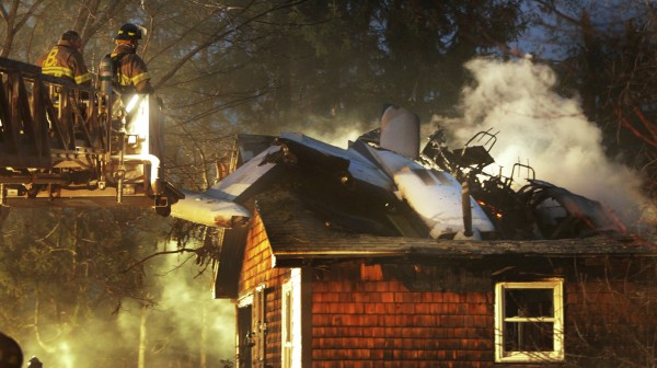 Firemen work at the scene where a small plane crashed into a house near the Biddeford Municipal Airport Sunday evening, April 10, 2011. The Federal Aviation Administration said the pilot of the plane died in the crash.