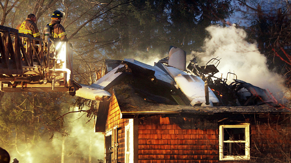 Firemen work at the scene where a small plane crashed into a house near the Biddeford, Maine, Municipal Airport Sunday evening. The Federal Aviation Administration said at least one person in the plane died in the crash.