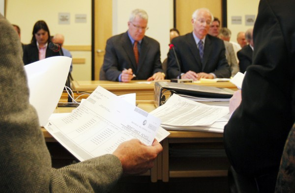 A member of the Legislature's Government Oversight Committee, reviews spending records during the questioning of Paul Violette, the former executive director of the Maine Turnpike Authority, Friday, April 15, 2011, in Augusta. Violette (in background at left) invoked his constitutional right against self-incrimination and refused to answer  questions about the authority's spending practices.