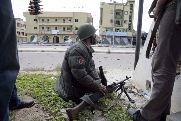 Libyan rebel fighters take up positions while battling pro-Gadhafi troops on Tripoli Street in the besieged city of Misrata, the main rebel holdout in Gadhafi's territory, Thursday, April 21, 2011.