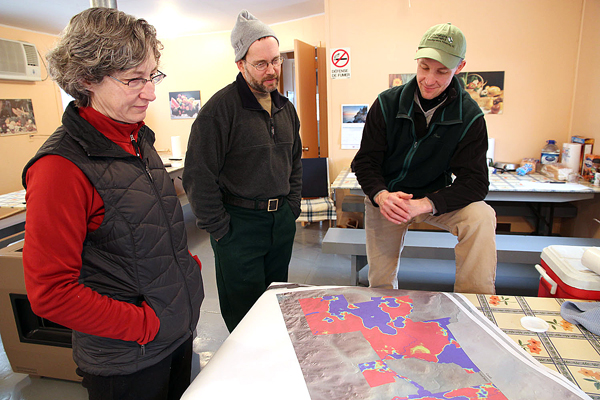 At the Baker Lake Camps, Nancy Sferra (from left) of The Nature Conservancy, Jim O'??Malley of Huber Resources and Bill Patterson of The Nature Conservancy check maps of the area in the St John Forest that the American Loggers crew will harvest.