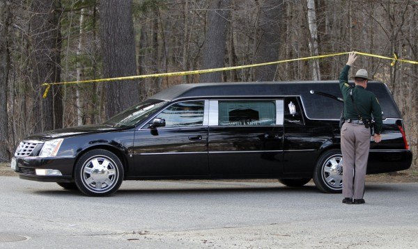 A New Hampshire State Police trooper holds up police tape so a hearse can pass underneath and leave Mount Cranmore in North Conway, N.H on Wednesday. Mount Cranmore is where Krista Dittmeyer's car was found still running on Saturday morning with her 14-month-old infant inside.