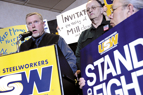 Surrounded by Maine workers and fellow labor representatives, Pat Carleton (left), President of the United Steel Workers Maine Labor Council, addresses the media during Friday morning's press conference in Bangor. Workers announced their invitation to President Obama and Senators Snowe and Collins to Millinocket and East Millinocket before making further decisions on free trade agreements. Next to him were U.S.W. international  representative Duane Lugdon (standing) and Maine Labor Council District 3 officer Gary McGrane (kneeling).