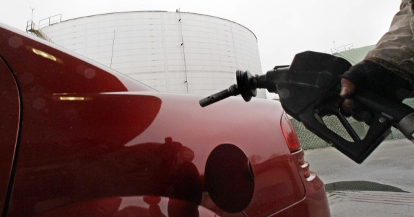 With a giant oil storage tank at rear, a gasoline attendant fills the tank of a car at a gas station in Quincy, Mass., Wednesday, April 20, 2011. Oil  climbed above $111 per barrel Wednesday as the dollar weakened and the government reported an unexpected drop in U.S. crude supplies.