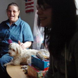 "Amy Cooper, on left, laughs as she pets dog Max and listens to her ""granddaughter"" Jazmine Stevens, talk in the living room of their Bangor home on Monday.  Although she is not biologically related to the teen, Cooper, age 65, has been raising Jazmine and her younger borther Chris since they were infants due to their birth mother's inability to care for them. Seeing a need for emotional and financial support among guardians in similar situations, Cooper is active in Maine Kids-Kin, a program of Families and Children Together, and often organizes fundraisers for the group."