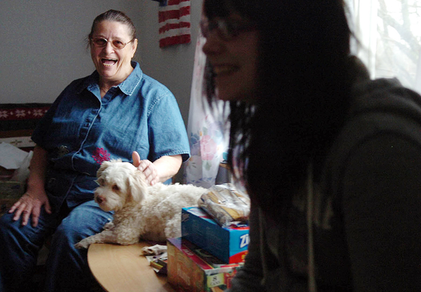 Amy Cooper, on left, laughs as she pets dog Max and listens to her &quotgranddaughter&quot Jazmine Stevens, talk in the living room of their Bangor home on Monday.  Although she is not biologically related to the teen, Cooper, age 65, has been raising Jazmine and her younger borther Chris since they were infants due to their birth mother's inability to care for them. Seeing a need for emotional and financial support among guardians in similar situations, Cooper is active in Maine Kids-Kin, a program of Families and Children Together, and often organizes fundraisers for the group.