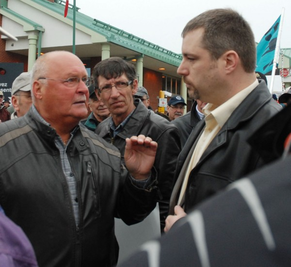 Retired mill worker Conrad Pelletier (left) defends his right to block international traffic between Madawaska, Maine, and Edmundston, New Brunswick, to a member of the Edmundston Police Department. Pelletier and close to 150 other retirees of the former Fraser Paper Co.'s Edmundston mill were demonstrating at the international bridge Thursday to gain attention and support in the wake of 35-percent cuts to their pension funds. The demonstration lasted close to two hours before police peacefully ushered the demonstrators away from the bridge.