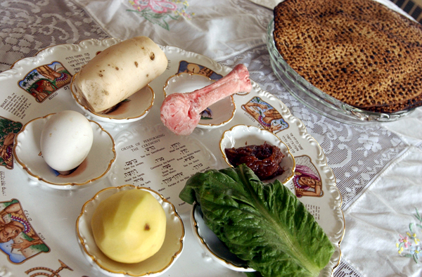 A roasted egg, boiled potato, romaine lettuce, Charoset (a sweet mixture of fruit, nuts and red wine), roasted lamb shank and horseradish are the traditional elements of a Seder plate. The breaking of matzo (upper right) also is part of the Seder.