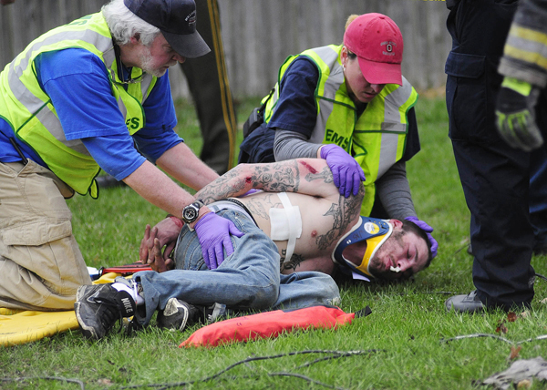 Williamstown Ambulance personnel tend to Jeffrey Davis, 26, of Johnson, Vt., in Williamstown, Vt., after Davis was shot by police and his vehicle ran over spikes, ending a high-speed chase that began on the interstate and wound through several central Vermont towns with Davis ramming his Jeep Grand Cherokee into several police cruisers.