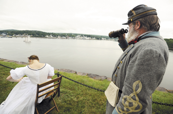 Ed Mann (right) of Aiken, S.C., watches the schooner Bowdoin from Fort Knox in Prospect as Molly Faulkner of Old Saybrook, Conn., works on embroidery.  Mann came to the Civil War re-enactment in the summer of 2010 as a spectator but couldn't resist getting suited up as the Confederate soldier he plays when in South Carolina as part of Hardee's Brigade South Guard.