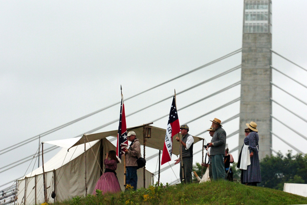 Spectators and reenactors  look out over the Penobscot River as the schooner Bowdoin sails up the river during the Battle at Fort Knox in Prospect in July 2010.