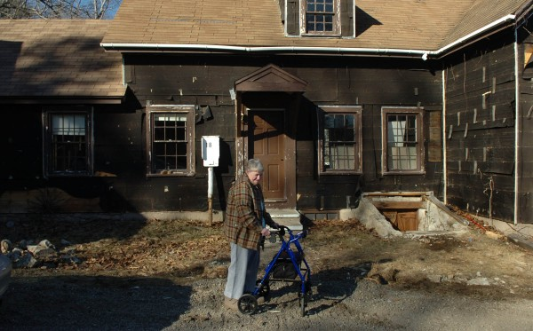 Ida Watson of Belfast walks in front of the Snow Hill Lodge in Lincolnville on Thursday, April 7, 2011. Watson and her late husband owned the motel for ten years in the 1980s and raised their two children there. Now in disrepair, the motel will be used as a practice burn for local firefighters.