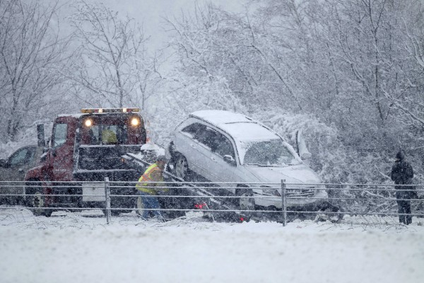 A motorist watches her car hauled onto a flatbed truck after she went off the highway on Interstate 295 in Freeport during Friday's spring snow storm.